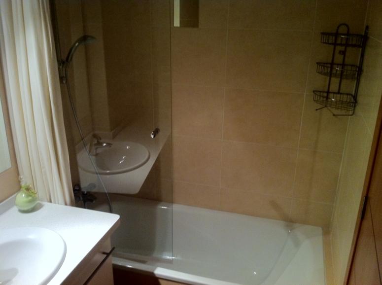 Badkamer met wastafel toilet en douche bad